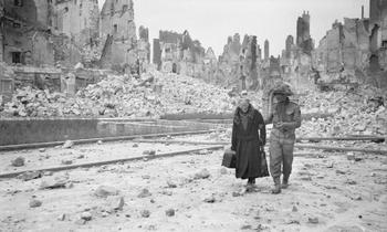 A British soldier in Caen after its liberation, gives a helping hand to an old lady amongst the scene of utter devastation.jpg