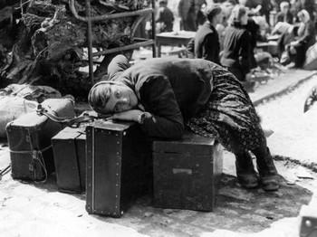 Ein erschöpfte russische Zwangsarbeiterin ruht sich im April 1945 in der Sammelstelle für Zwangsverschleppte in Würzburg auf Gepäckstücken aus.jpg