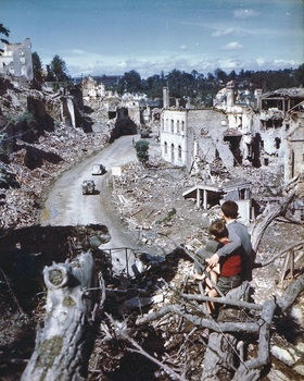 French children watch as U.S. jeeps transition through the devastation in Saint-Lô following liberation, 1944.jpg