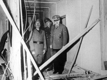 Hitler mit Mussolini und Chefdolmetscher Paul-Otto Schmidt in der zerstörten Lagebaracke.jpg