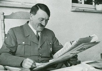 Hitler smiles while reading newspaper.jpg
