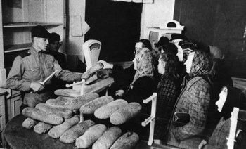 A Soviet soldier uses a German officer's dagger to cut bread given to German women in post-war Berlin.jpg