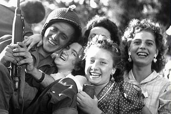 A group of French teenage girls hugs a soldier during the liberation of Paris.jpg