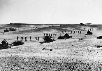 Australian troops marching behind the tanks during a rehearsal of the offensive in the sands of North Africa.jpg