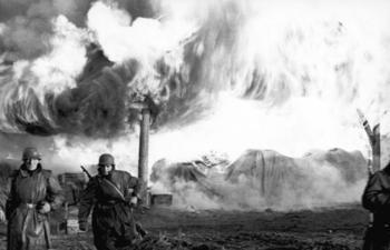 Deutsche Soldaten vor einem brennenden Dorf 1941.jpg