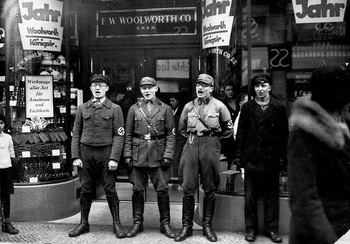 Four Nazi troops sing in front of the Berlin branch of the Woolworth Co. store during the movement to boycott Jewish presence in Germany, in March, 1933.jpg