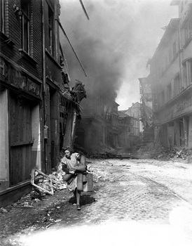 German woman carrying a few possessions runs from burning building.jpg
