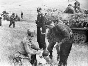 Leibstandarte at artillery post with Russian POW Kursk 1943.jpg
