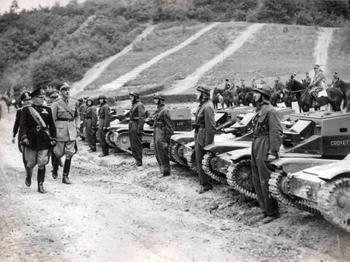 Mussolini con alcuni ufficiali militari e Starace passa in rassegna soldati accanto a carri armati.jpg