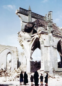 Nuns and some children look on at the ruins of an almost totally destroyed church.jpg