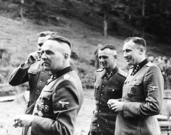 Rudolf Höss (left) and other SS officers gather for drinks in a hunting lodge.jpg