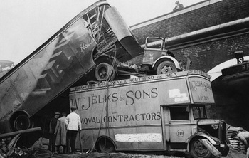 The force of a bomb blast in London piled these furniture vans atop one another in a street after a raid on December 5, 1940..jpg
